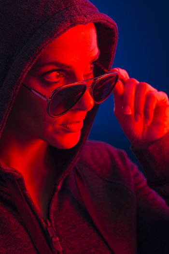 Woman wearing sunglasses in illuminated room