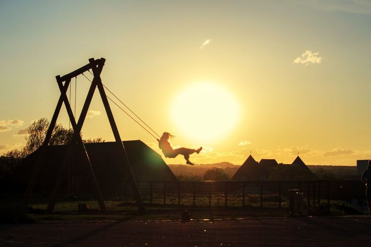 The dream of flying. Warm Day Dreaming Kids Childhood Childhood Memories Photography Swing Swinging City Sunset Silhouette Oil Pump Sky Architecture Built Structure Shining Sun Sunbeam Lens Flare Bright #urbanana: The Urban Playground