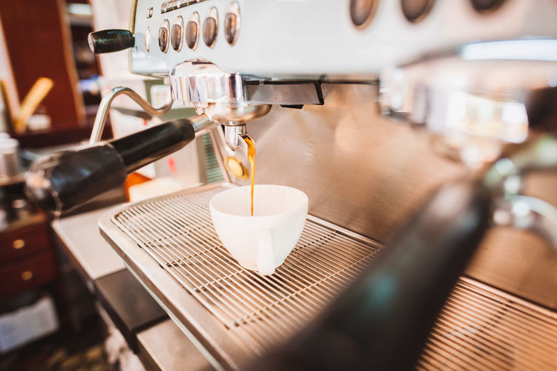 Coffee Pouring From Espresso Maker In Cup At Shop