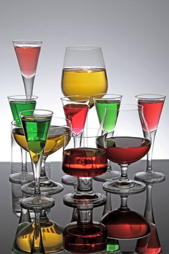 Close-Up Of Various Colorful Cocktails On Table Against Gray Background