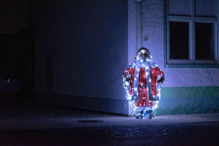 Illuminated santa claus statue on road at night