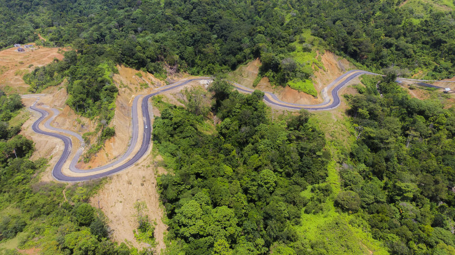 High angle view of winding road amidst trees in forest