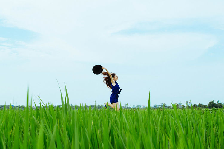 Carefree woman running in rice field against sky