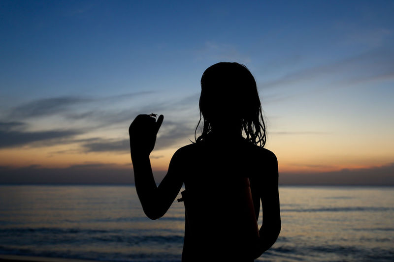 Silhouette Girl With Crab At Beach Against Sky During Sunset