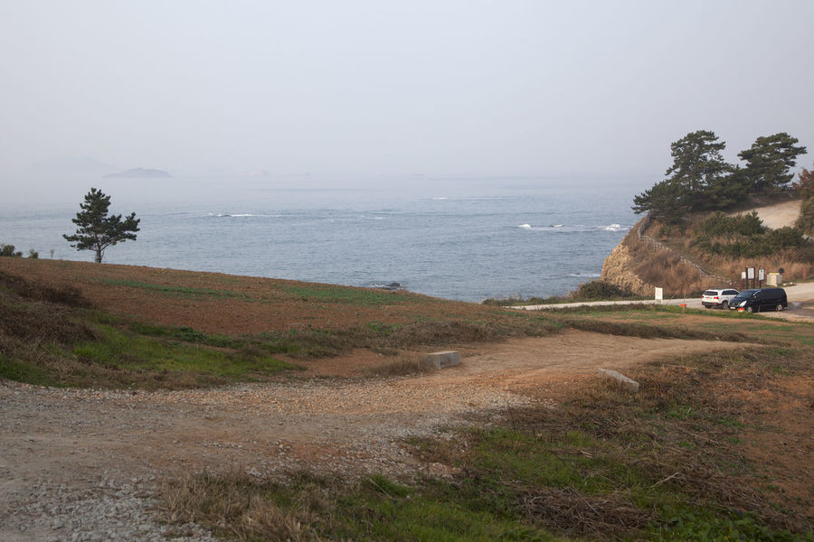 Seaside view of Gyeokpo Beach in Byeonsan, Buan, Jeonbuk, South Korea Beach Beauty In Nature Cliff Day Grass Gyeokpo Horizon Over Water Landscape Nature Outdoors Real People Scenics Sea Sky Tranquil Scene Tranquility Tree Water