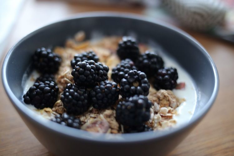 Close-up of blackberries on granola in bowl at table