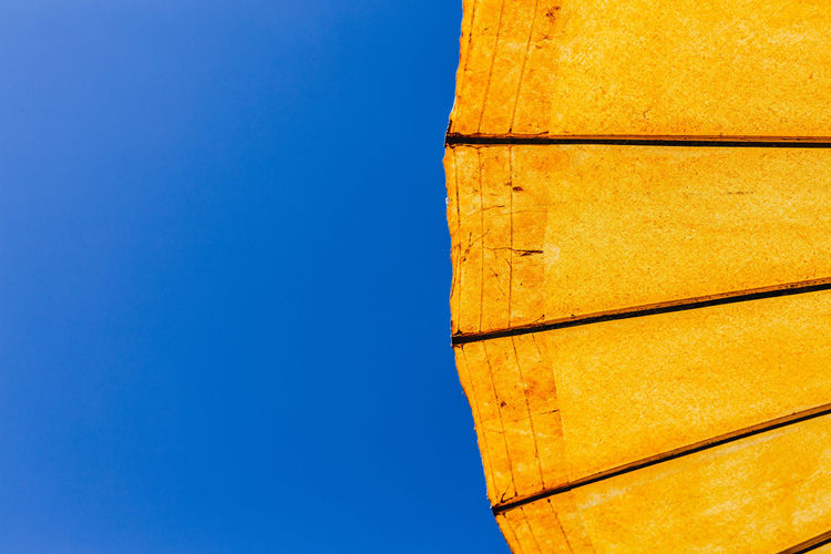 A pattern from an umbrella. no people day yellow Low angle view outdoors pattern blue Architecture Clear sky sky Copy Space built structure Nature Sunlight building exterior wall - building feature wood - material brown building orange color directly below minimal Minimalist Architecture Business No People Day Yellow Low Angle View Outdoors Pattern Blue Architecture Clear Sky Sky Copy Space Built Structure Nature Sunlight Building Exterior Wall - Building Feature Wood - Material Brown Building Orange Color Directly Below Minimal