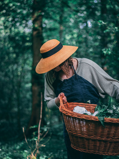 Midsection of man holding hat in basket