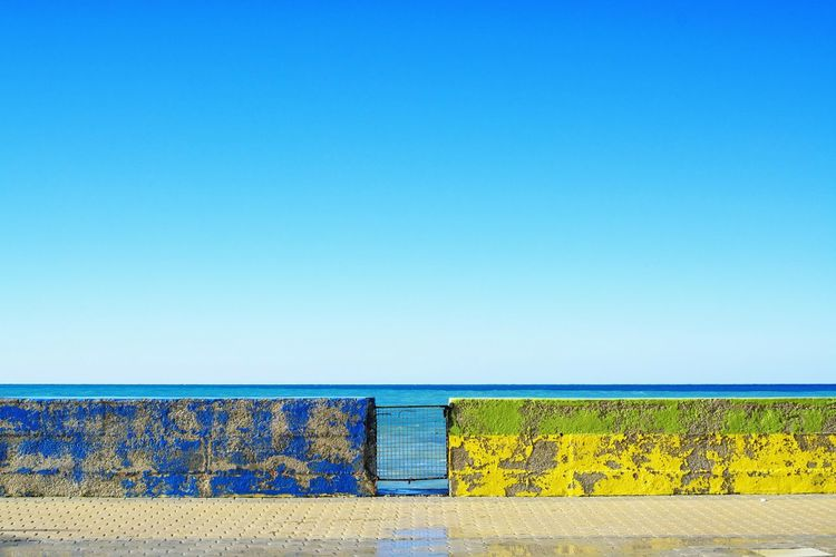 Yellow wall against clear blue sky