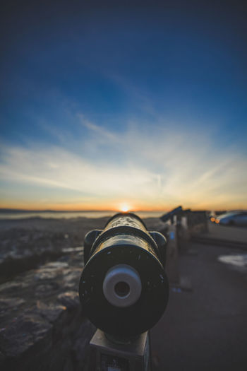 Close-up of coin-operated binoculars at beach against sky during sunset