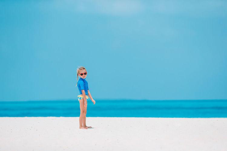 Boy standing on beach against blue sky