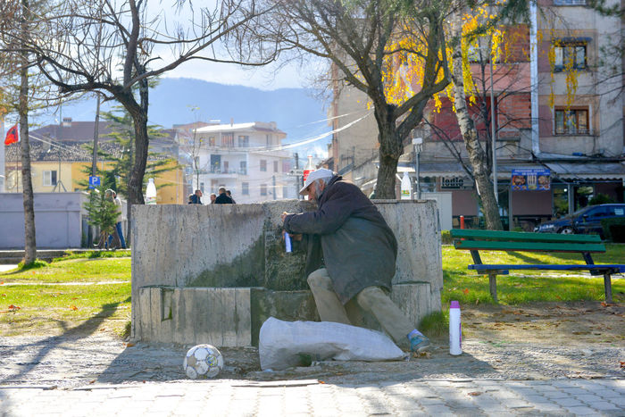 homeless man on a public drinking fountain.\ pogradeci, albania, dec. 9.2017 December Drinking Water Sunny Architecture Bare Tree Bottle Building Exterior Built Structure Can Cold Day Homeless Men Nature One Person Outdoors People Poverty Public Water Fountain Real People Sitting Sky Social Issues Tree Water