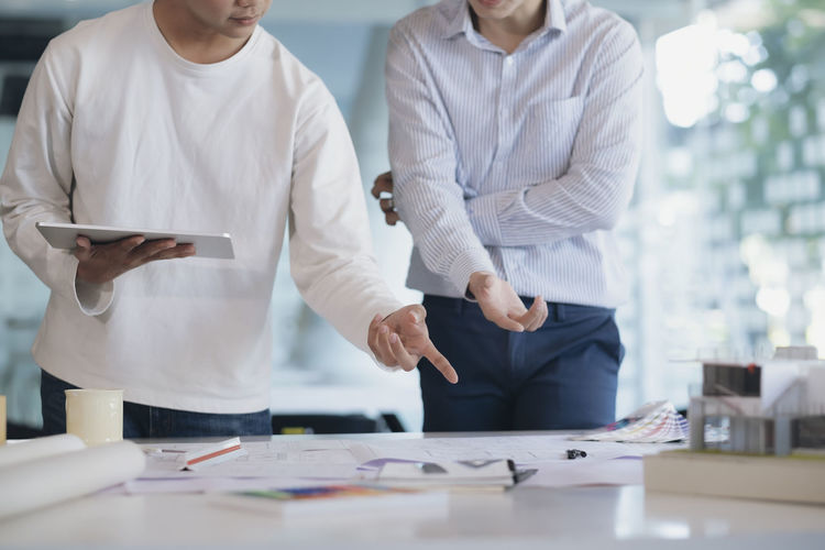 Midsection of colleagues discussing at desk in office