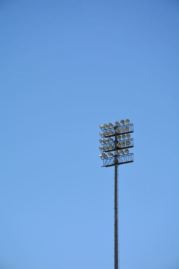Low angle view of stadium lights isolated against clear blue sky