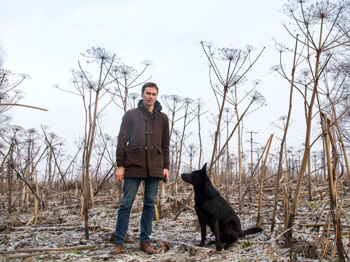 Portrait of man training dog against bare trees on land during winter