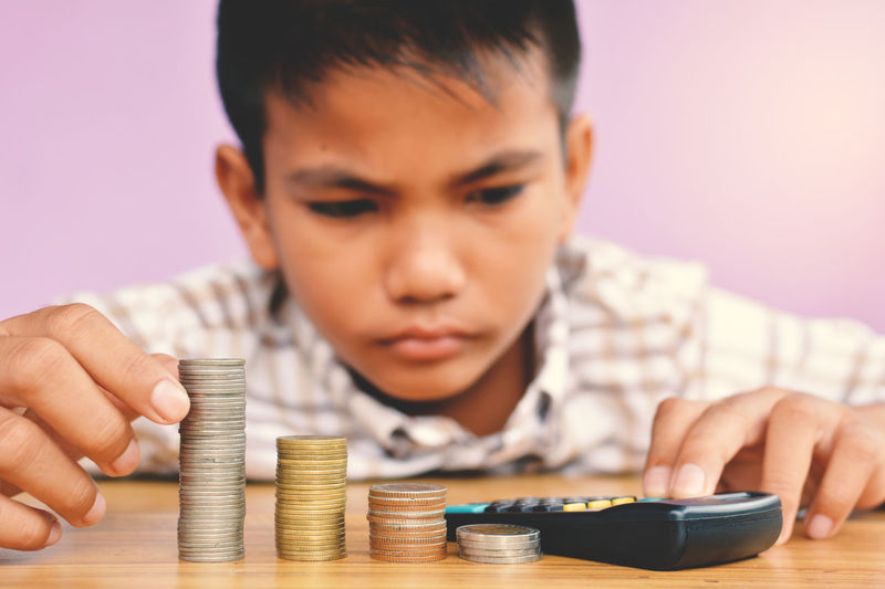 Close-Up Of Boy Counting Coins By Calculator At Table Against Wall