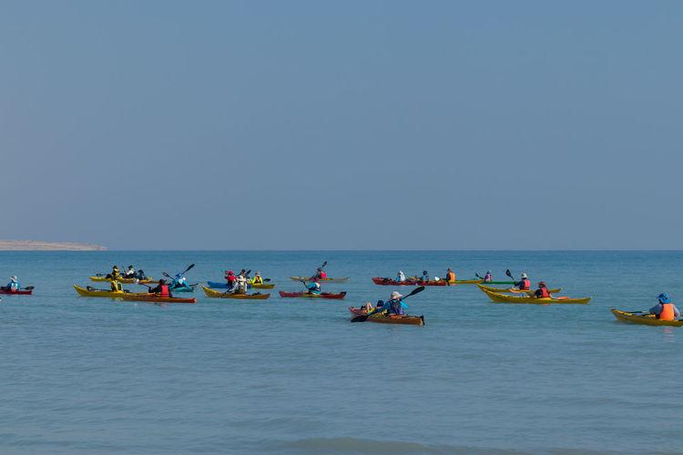 People enjoying in sea against clear sky