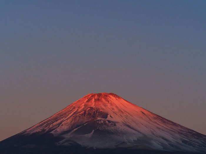 Low angle view of volcanic mountain against clear sky