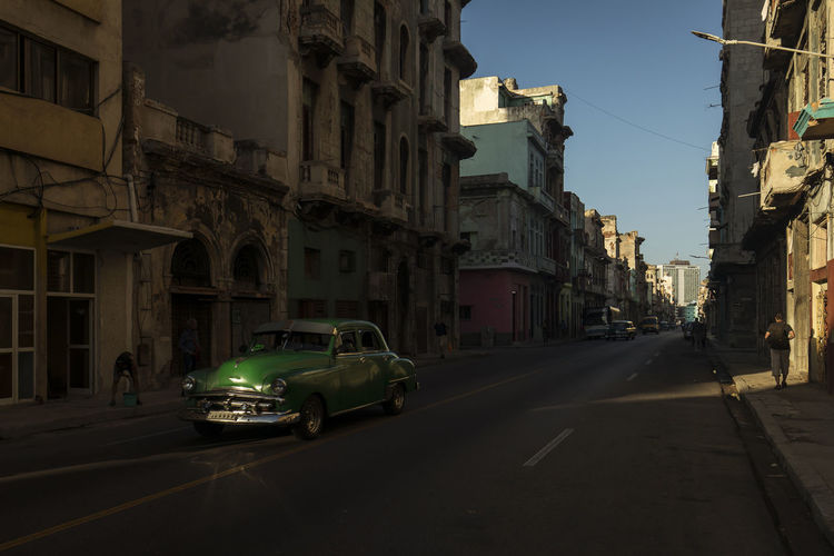 Cars on road amidst buildings in city