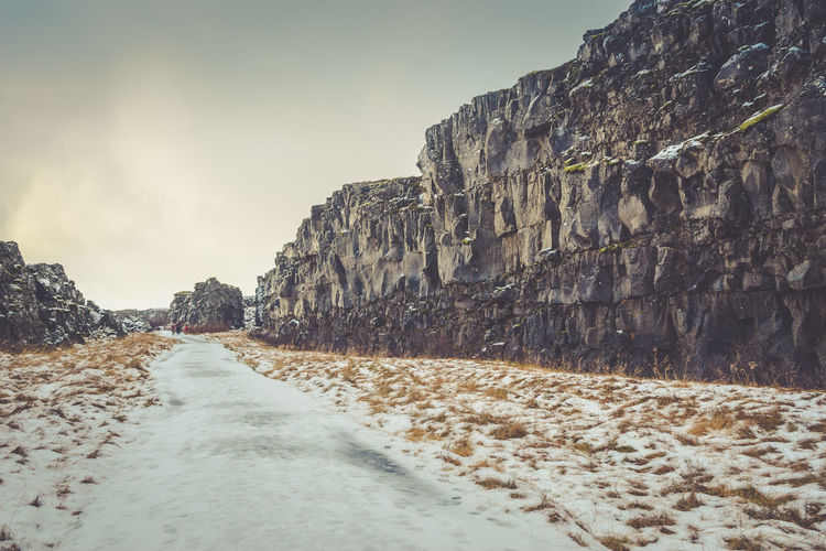 A walking path covered in ice, lined by rock, in the icelandic national park thingvellir