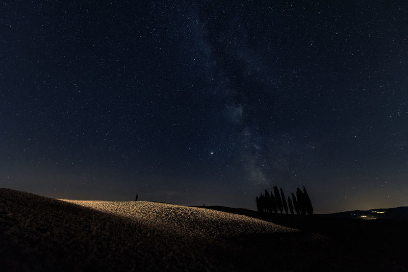 Scenic view of field against sky at night, milky way in tuscany