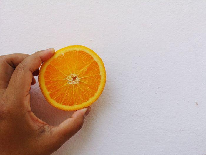 Cropped image of hand holding orange
