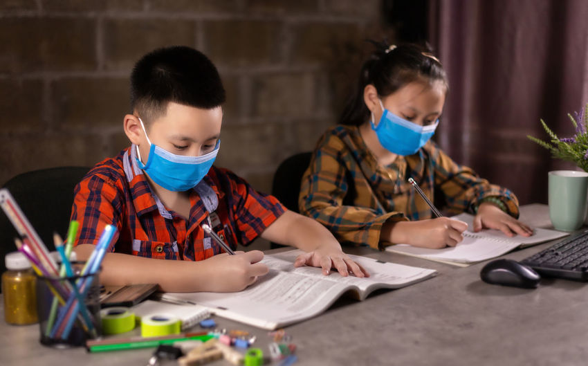 View of boy and girl wearing flu mask studying at home