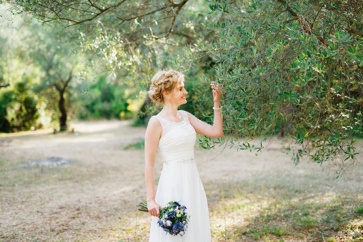 Bride holding bouquet standing against plants