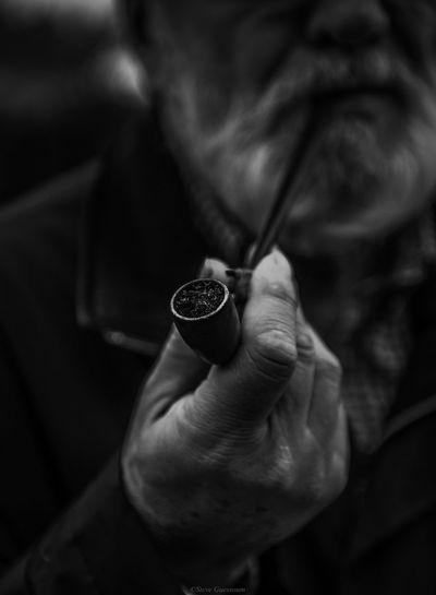 Midsection Of Senior Man Holding Smoking Pipe
