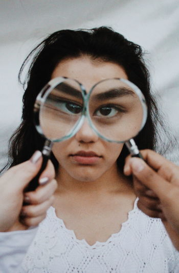 Portrait of young woman holding magnifying glass over eyes