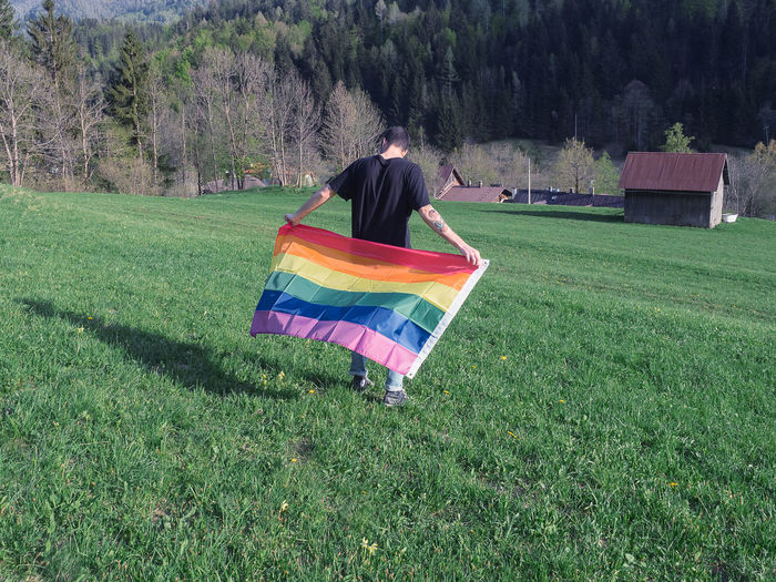 Rear View Of Man Rainbow Flag In Field