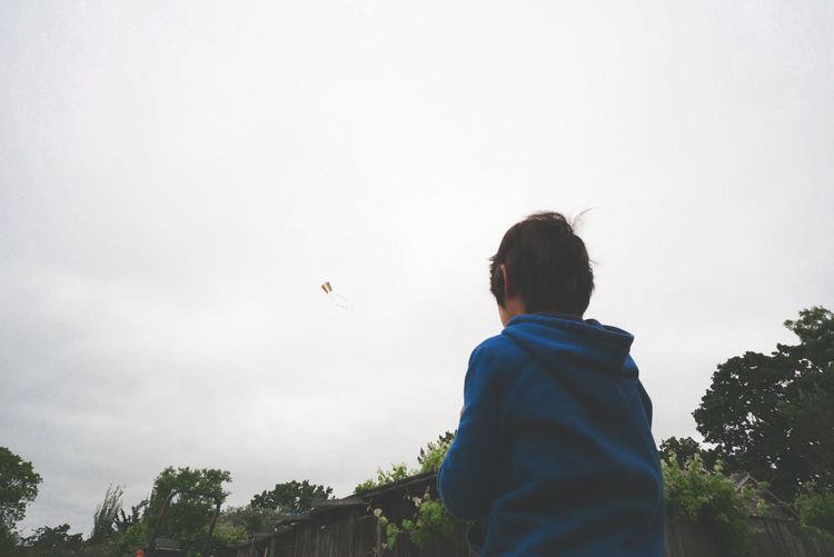 Low angle view of boy flying kite