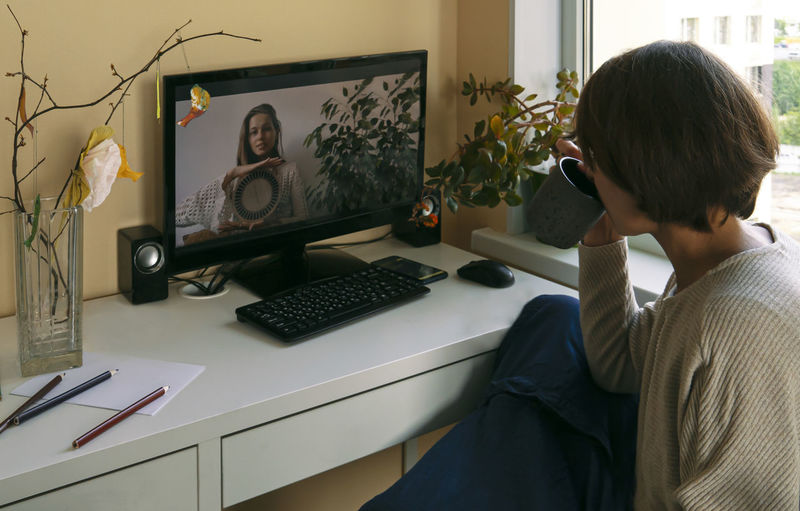 Woman video conferencing with friend over computer at home