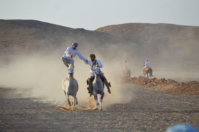 People Riding In Desert