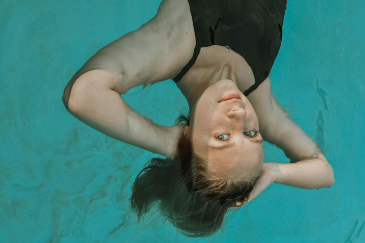 High angle portrait of young woman in swimming pool