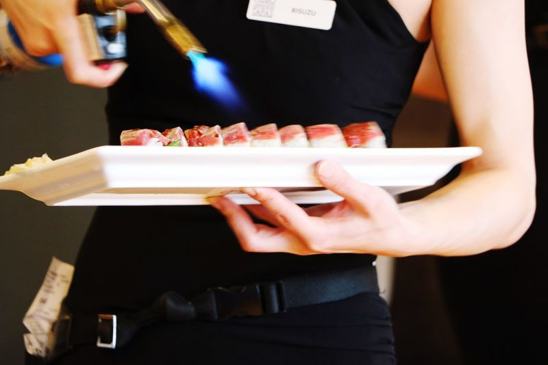 Midsection of woman with  sushi plate