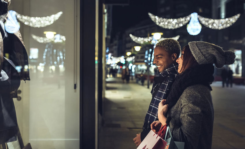 Man and woman standing in city at night