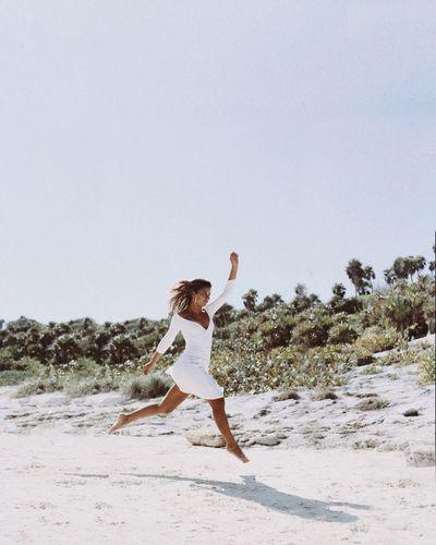 Full length of man walking on beach against clear sky