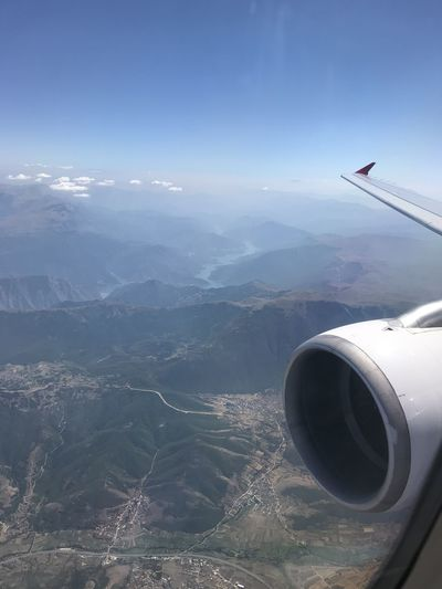 Airplane flying over mountains against sky