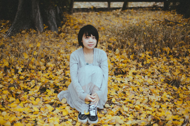 Portrait Of Young Woman Sitting On Ground