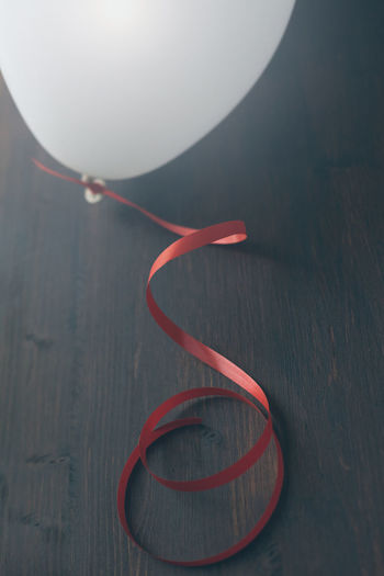 Close-Up Of Ribbon Tied To Balloon On Table