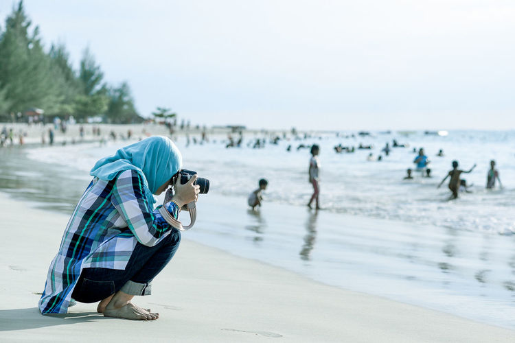 Side view of woman photographing while crouching against people at beach