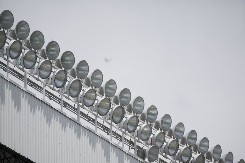 View of the lighting system of a football stadium. Stadium Abundance Architecture Arrangement Built Structure Clear Sky Copy Space Day In A Row Large Group Of Objects Lighting Equipment Low Angle View Nature No People Order Outdoors Pattern Repetition Side By Side Sky