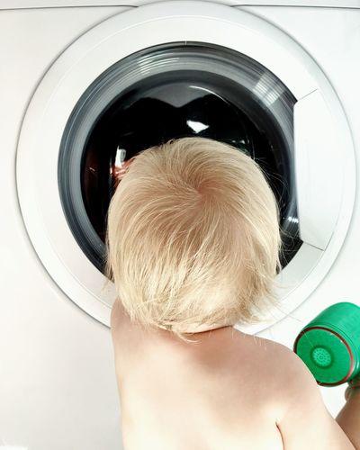 Rear view of boy looking at washing machine