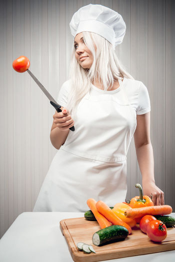 Woman cook indoors, weight loss concept Apron Cook  Cooking Culinary Diet Eating Uniform Vegetarian Food Weight Loss Woman Blond Hair Caucasian Chef Chef Hat Concept Conceptual Dieting Healthy Eating Healthy Food One Person Tomato Vegetable Vegetables Young Adult Young Women