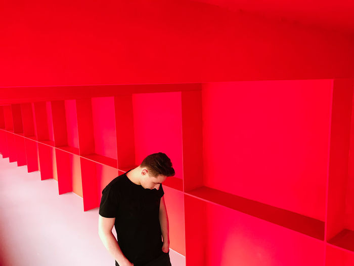 Red Dimension Bright EyeEm Best Shots Architecture Bold Built Structure Casual Clothing Contemplation Front View Indoors  Leisure Activity Lifestyles Looking Minimalism One Person Real People Red Standing Three Quarter Length Waist Up Wall - Building Feature Women Young Adult Young Men