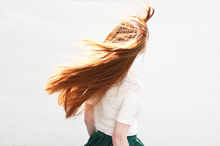 Rear view of woman with brown hair standing against white background