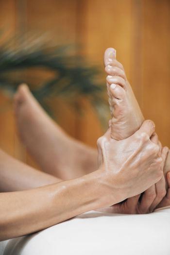 Ayurvedic reflexology foot massage, ayurveda practitioner pressing meridian points on female foot.