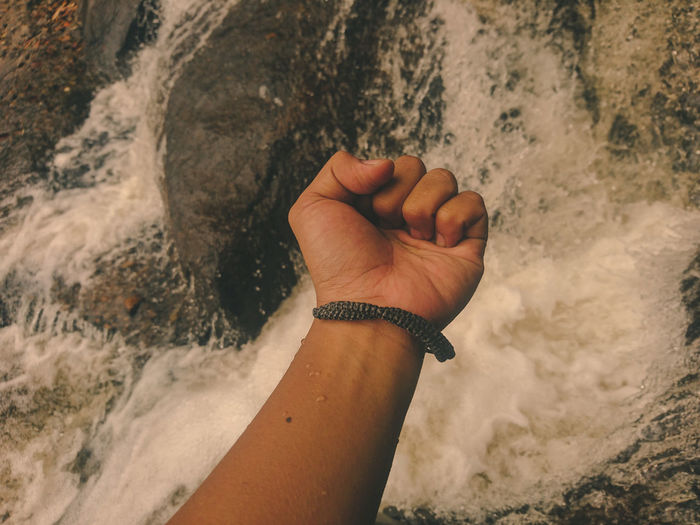 High angle view of wrist over flowing water at stream