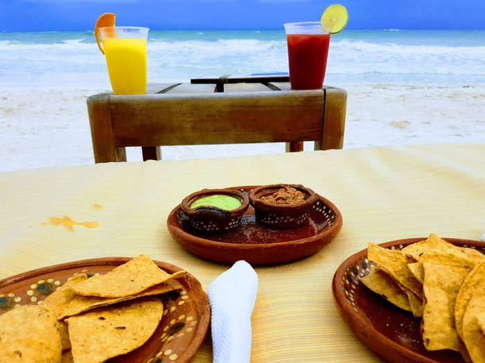 Close-up of food and drink on tables at beach